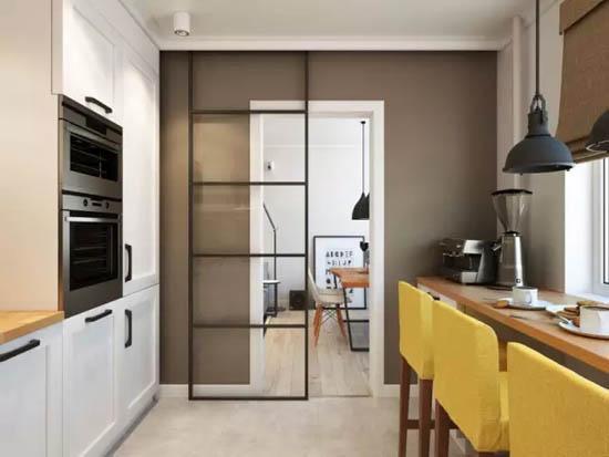 厨房的地砖与客厅的木地板被一道透明的黑框移门